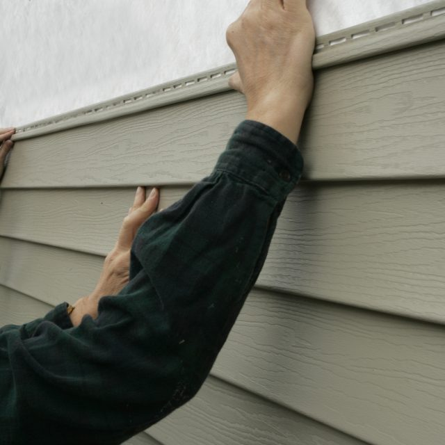 Workers installing siding on a house